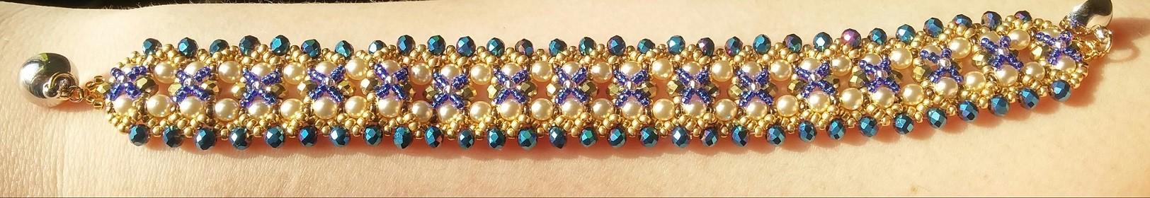 Bracciale dorato perle bianche e perle blu aperto